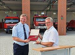 Bürgermeister Golde (r.) übergibt symbolisch den Schlüssel an Michael Krüger, Zugführer des 4. Löschzuges